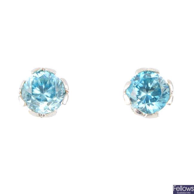A pair of zircon and diamond stud earrings.