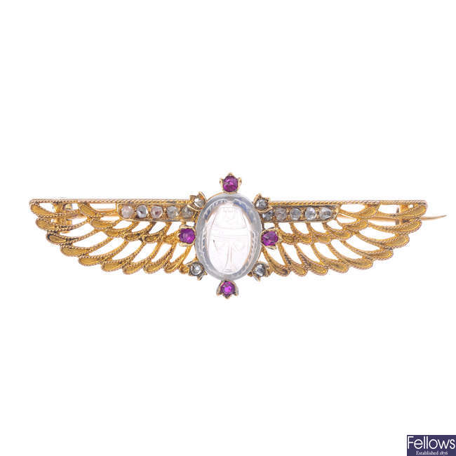 An early 20th century Egyptian Revival gold, diamond and gem-set brooch.