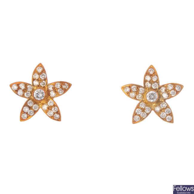A pair of diamond floral earrings.