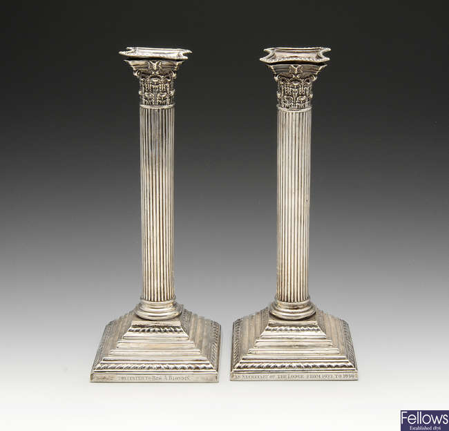 A pair of late Victorian silver mounted candlesticks.