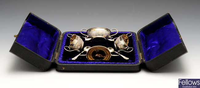 An Edwardian cased set of four silver salts together with four matched salt spoons.