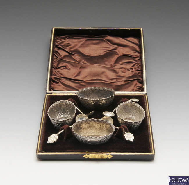 A late Victorian cased set of four silver salts together with four salt spoons.