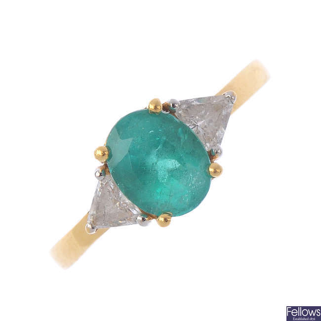 An 18ct gold emerald and diamond three-stone ring.