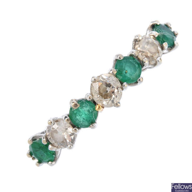 An emerald and diamond half-circle eternity ring.