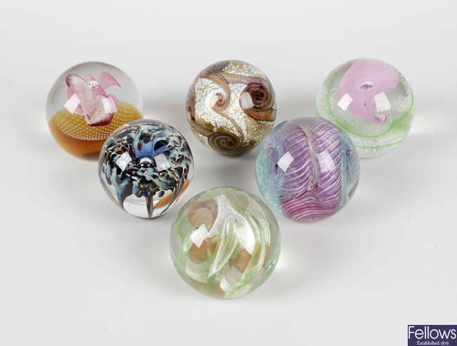 Twenty one various Caithness glass paperweights, together with a mixed selection of other assorted glass paperweights.
