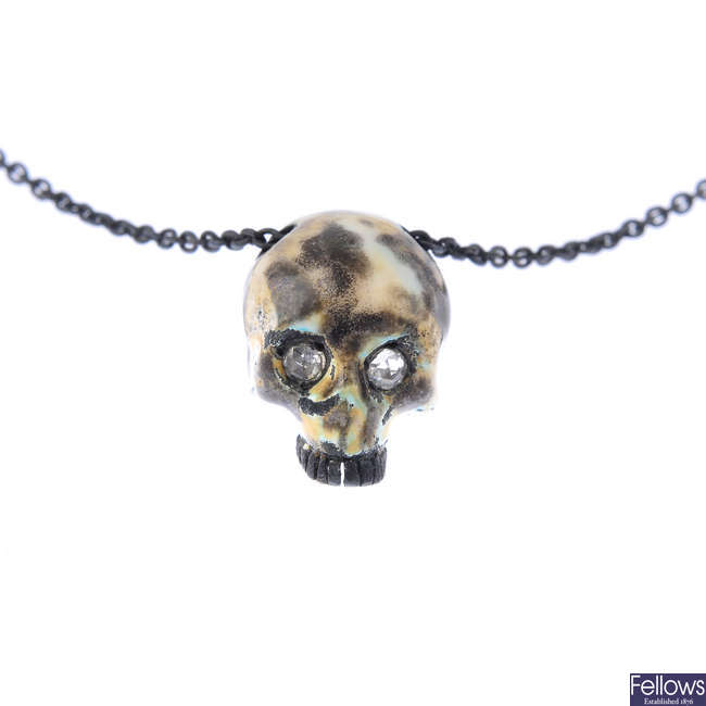 A diamond and enamel skull pendant, with chain.