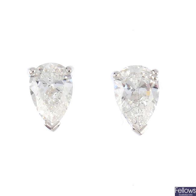 A pair of pear-shape diamond stud earrings.