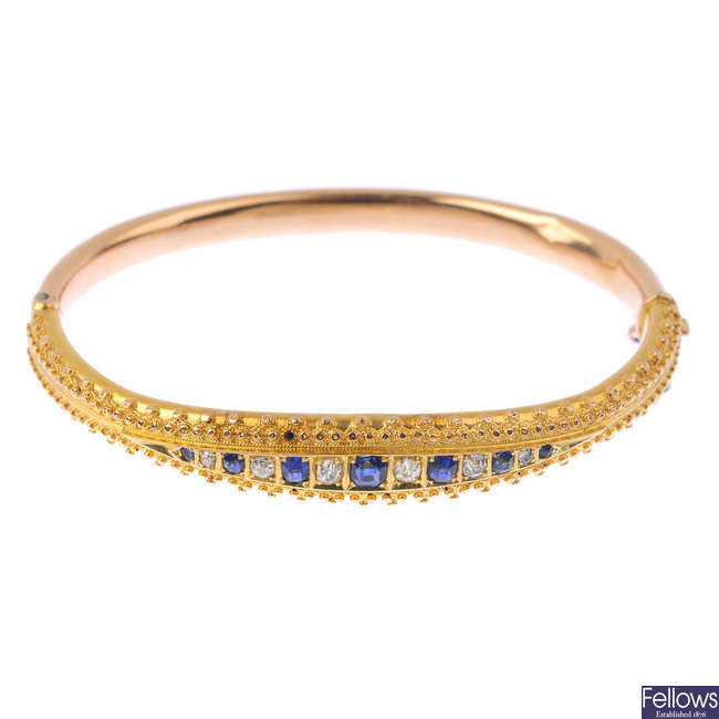 An early 20th century 15ct gold sapphire and diamond hinged bangle.