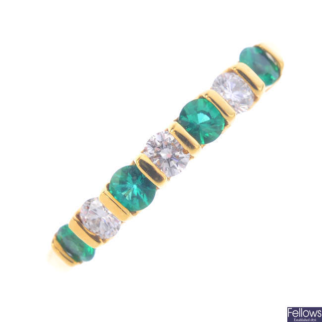 An 18ct gold emerald and diamond seven-stone ring.