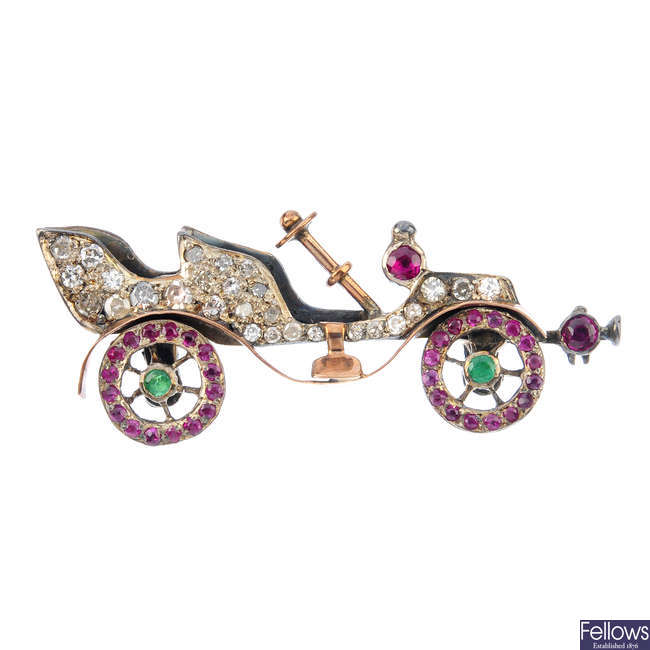 An early 20th century silver and gold, diamond and gem-set car brooch.