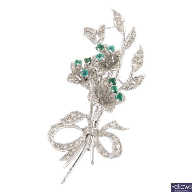 An emerald and diamond floral brooch.