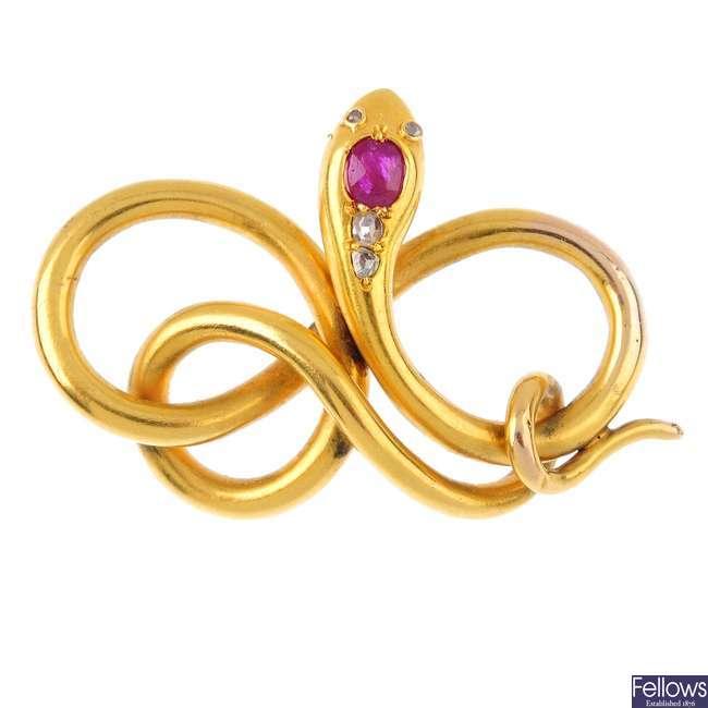 An early 20th century gold gem-set snake pendant.