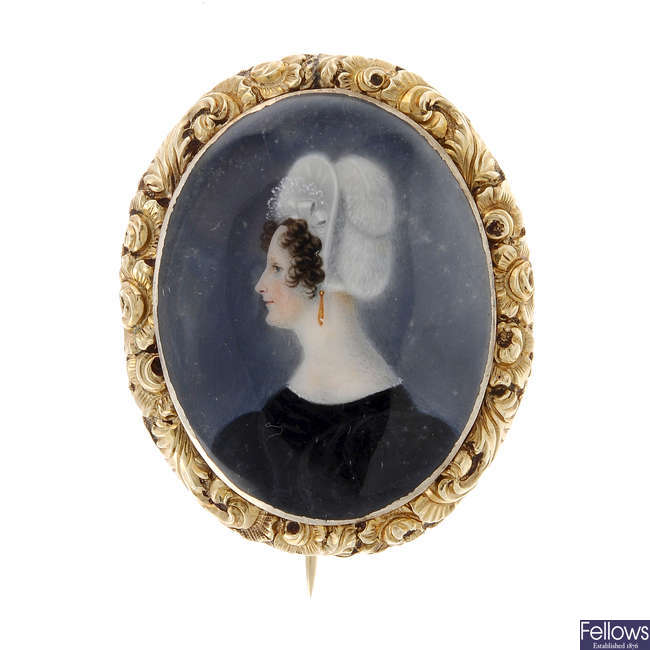 An early 19th century gold, hand painted portrait brooch.