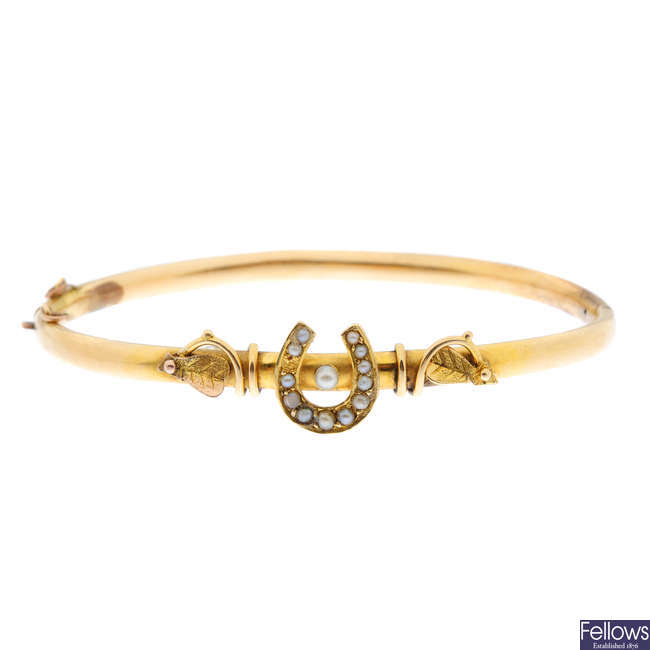 An early 20th century gold split pearl hinged bangle.