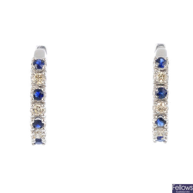 A sapphire and diamond pendant and earrings.
