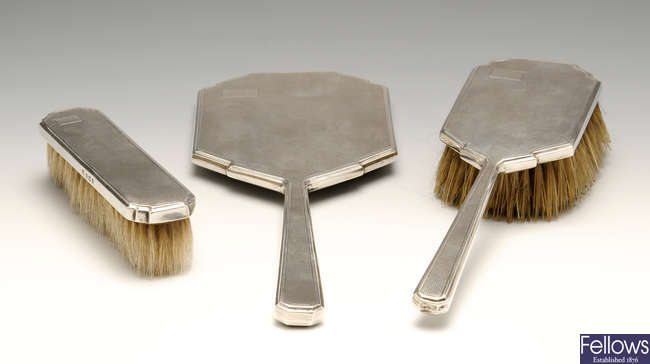 An Art Deco silver mounted three piece dressing table set.