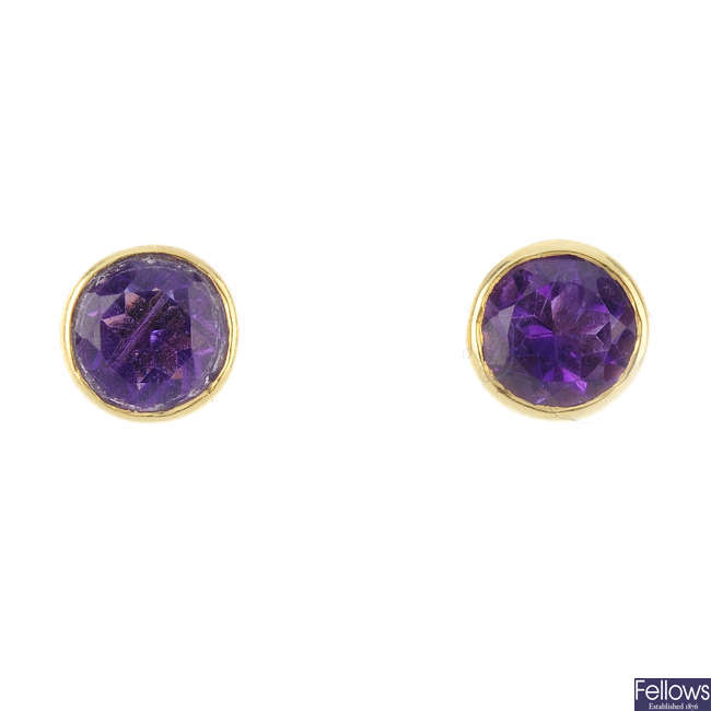 A band ring and a pair of amethyst stud earrings.