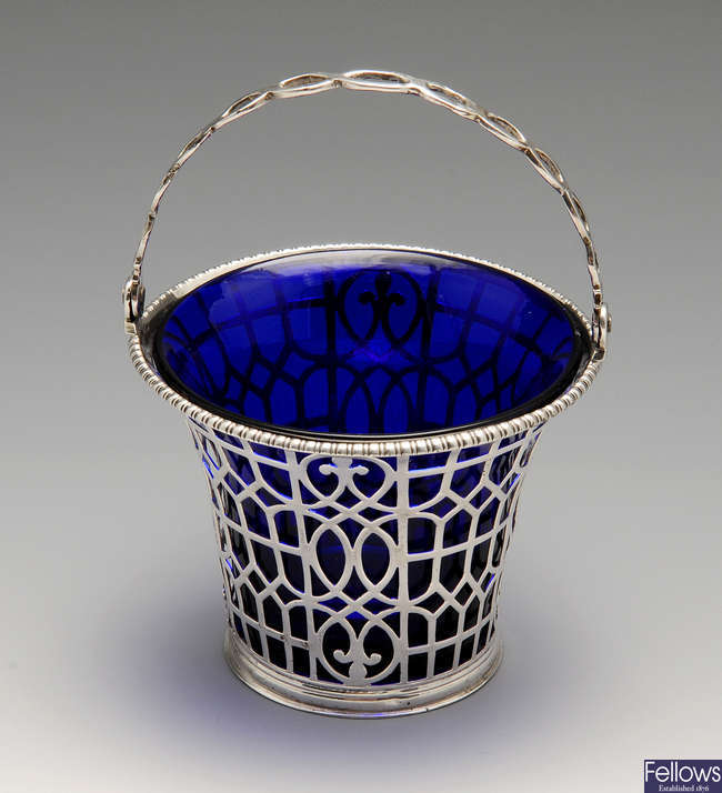 An early George III pierced silver swing-handled basket with glass liner.