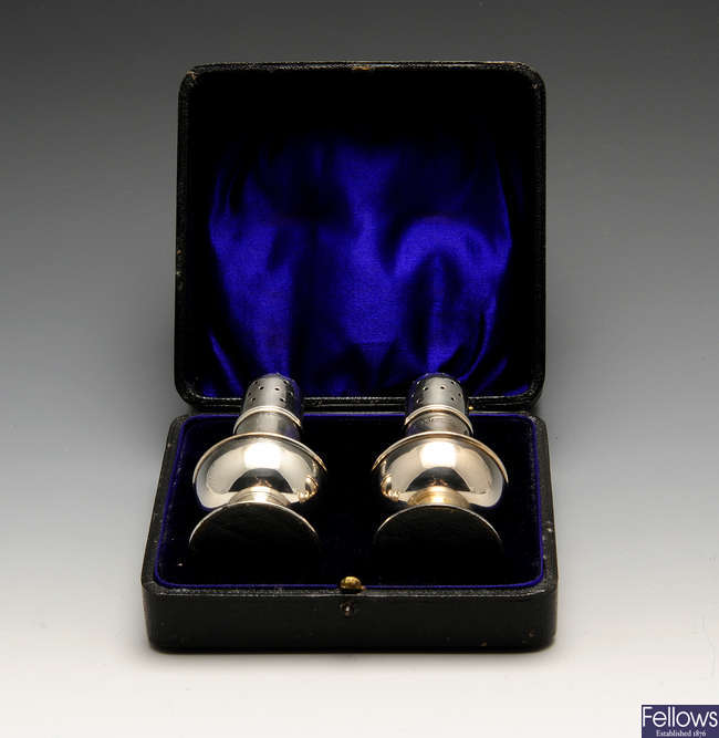 A cased pair of Edwardian silver pepper pots & a later cased condiment set. (2).