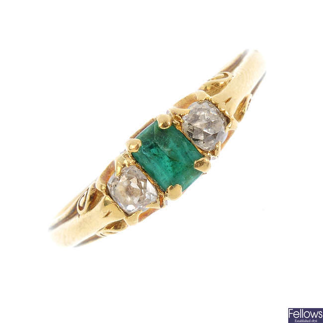 An emerald and diamond three-stone ring.