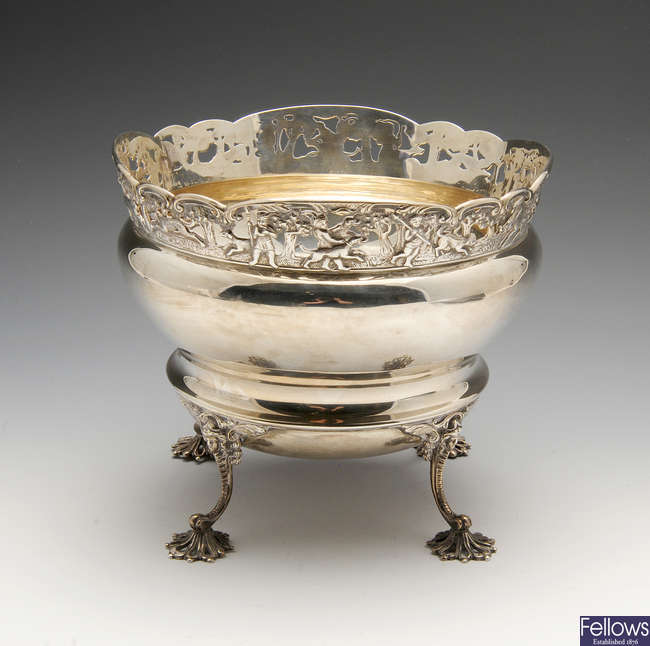 An Edwardian silver fruit bowl with hunting scene border.