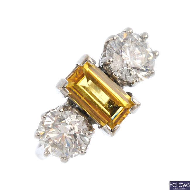 An 18ct gold yellow sapphire and diamond three-stone ring.