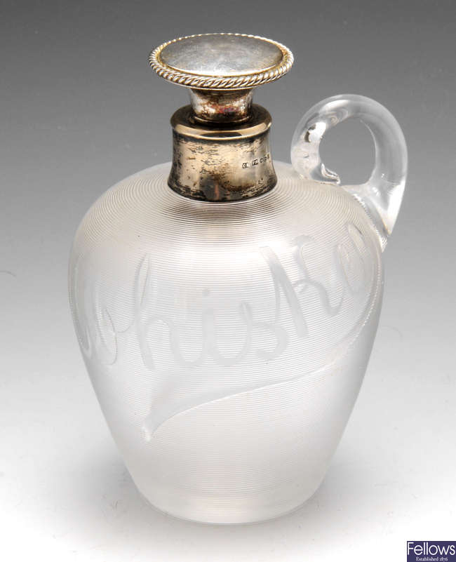 A late Victorian silver mounted glass 'Whiskey' jug or bottle.