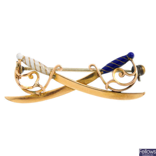 An early 20th century gold and enamel regimental crossed swords brooch.