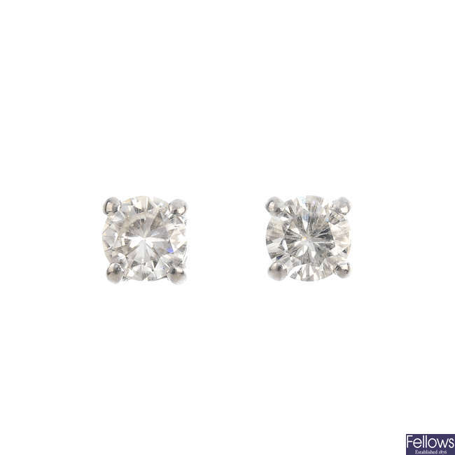 A diamond single-stone ring and a pair of synthetic moissanite stud earrings.