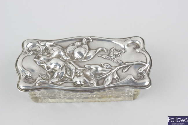 An Art Nouveau silver-lidded cut glass toiletry box.