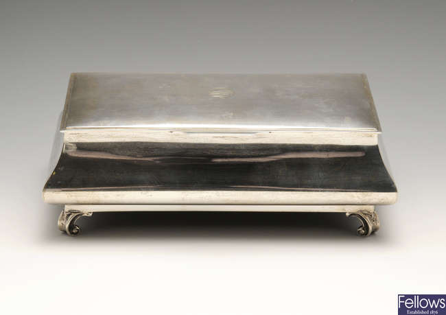 An early 20th century silver mounted table cigarette box on scroll feet.