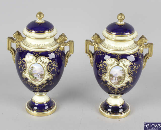 A pair of Coalport urns and covers.