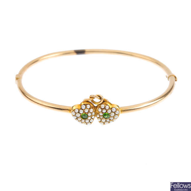 An early 20th century 9ct gold demantoid garnet and split pearl hinged bangle.