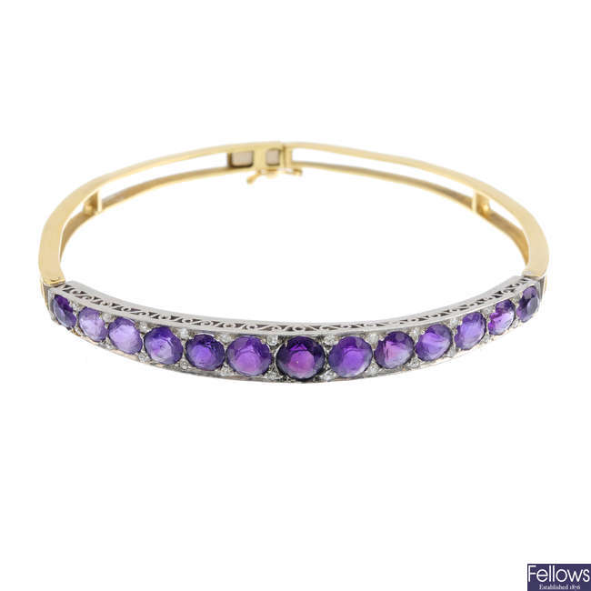 An early 20th century platinum and 18ct gold amethyst and diamond hinged bangle.