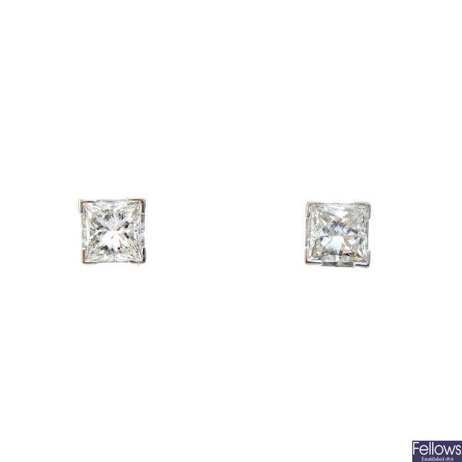 A pair of diamond stud earrings.