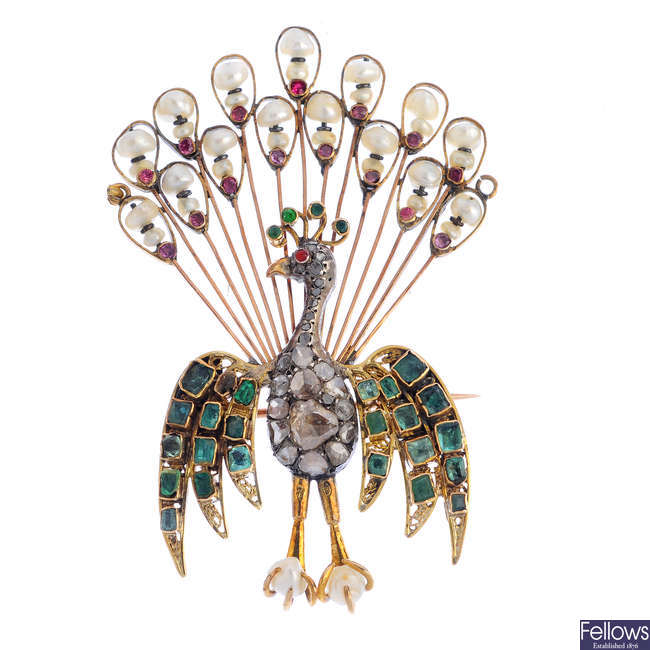 An early 20th century diamond, emerald, ruby and seed pearl peacock brooch.