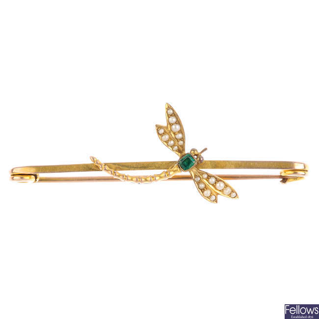 An early 20th century emerald and split pearl dragonfly bar brooch.