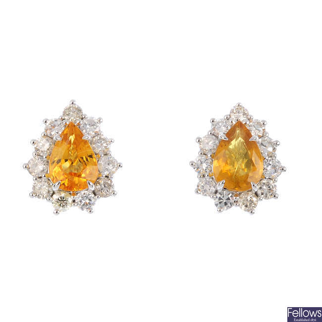 A pair of yellow sapphire and diamond cluster earrings.