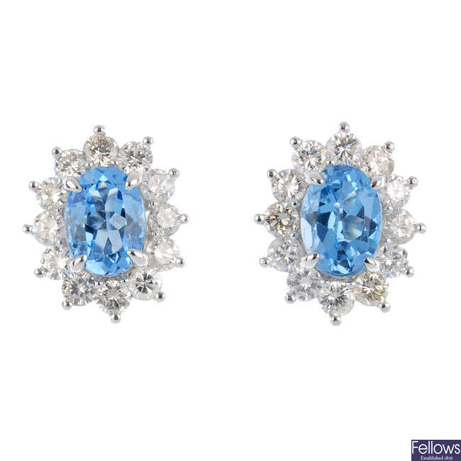 A pair of blue topaz and diamond earrings.