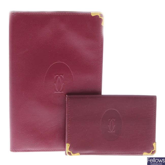 CARTIER - two Bordeaux leather wallets.