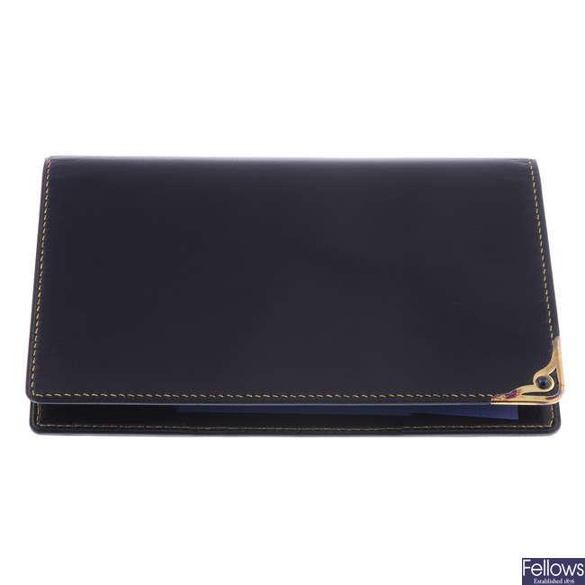 CARTIER - a black leather wallet.