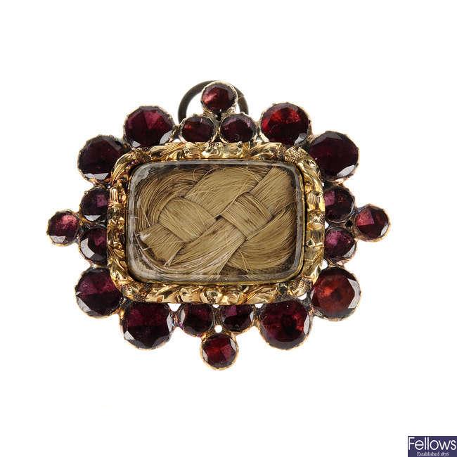An early Victorian garnet and hair memorial brooch.