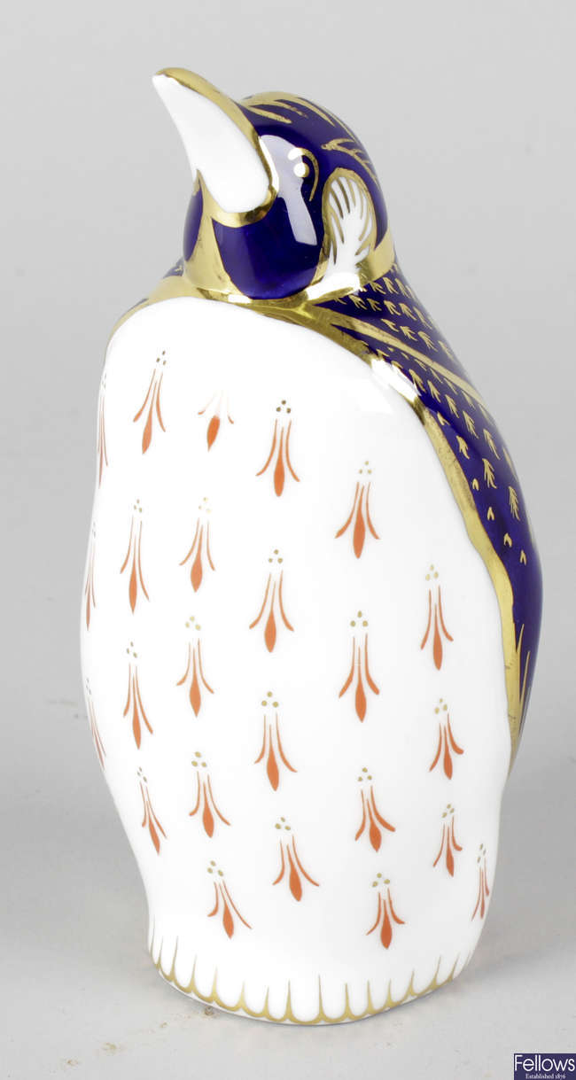 A Royal Crown Derby porcelain paperweight modelled as a penguin.