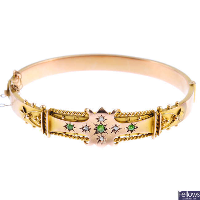 An Edwardian 9ct gold demantoid garnet and diamond hinged bangle.