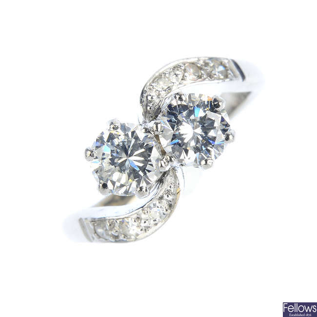 A mid 20th century 18ct gold and platinum diamond two-stone crossover ring.