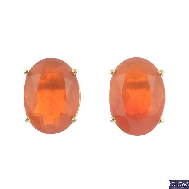 A pair of oval-shape fire opal single-stone stud earrings.