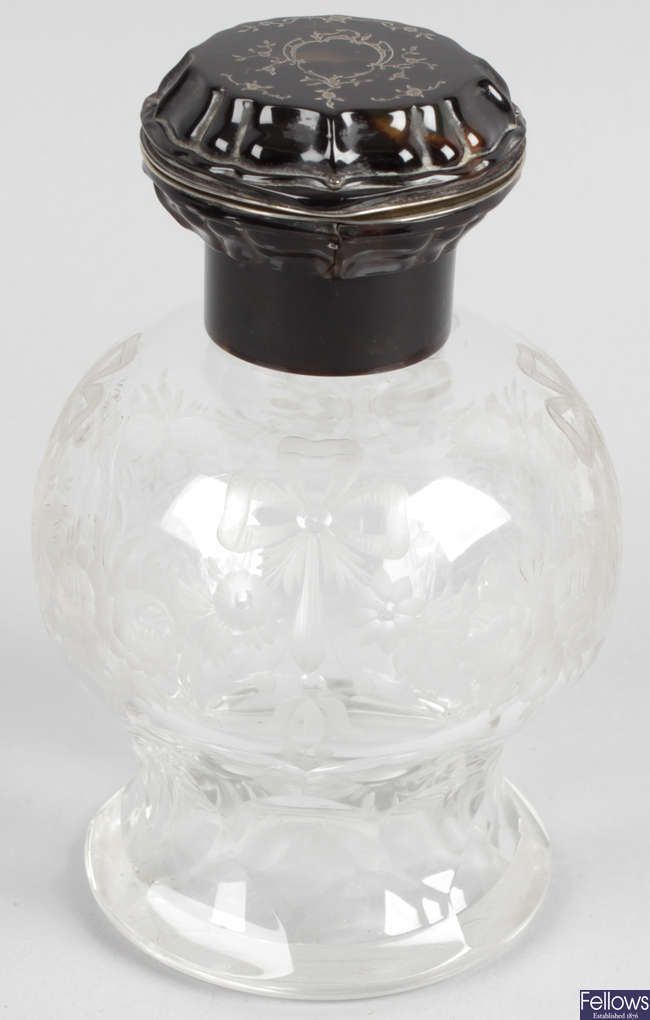 An early 20th century tortoiseshell and white metal mounted cut glass scent bottle.