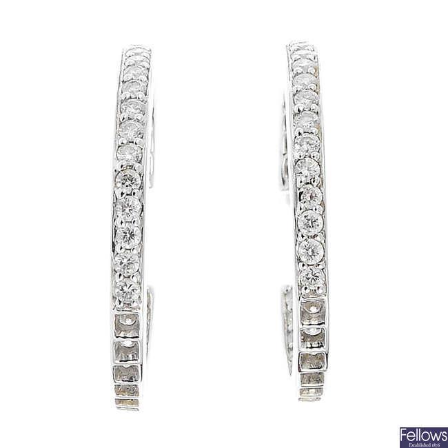 A pair of diamond hoop earrings.