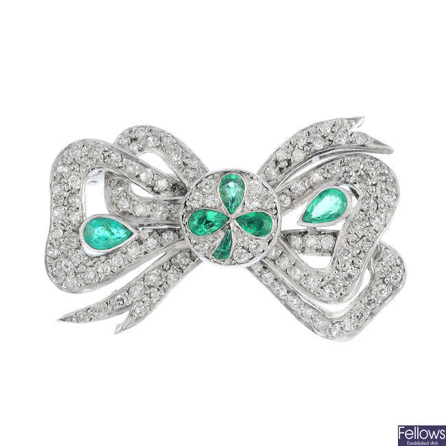 An early 20th century emerald and diamond bow brooch.