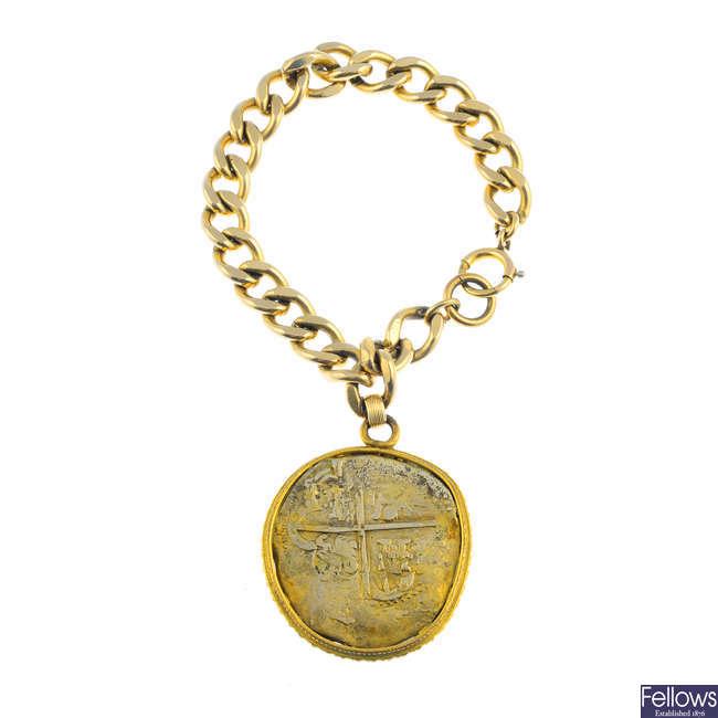 A bracelet, suspending a Spanish coin pendant.